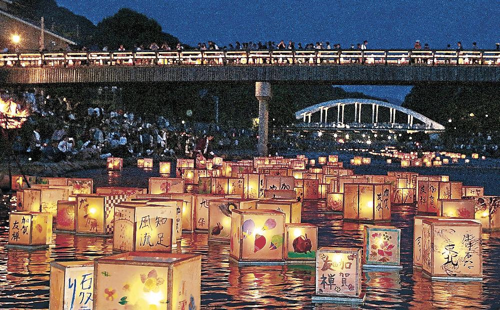 ゆっくりと流れ、水面を彩る燈ろう=金沢市の浅野川