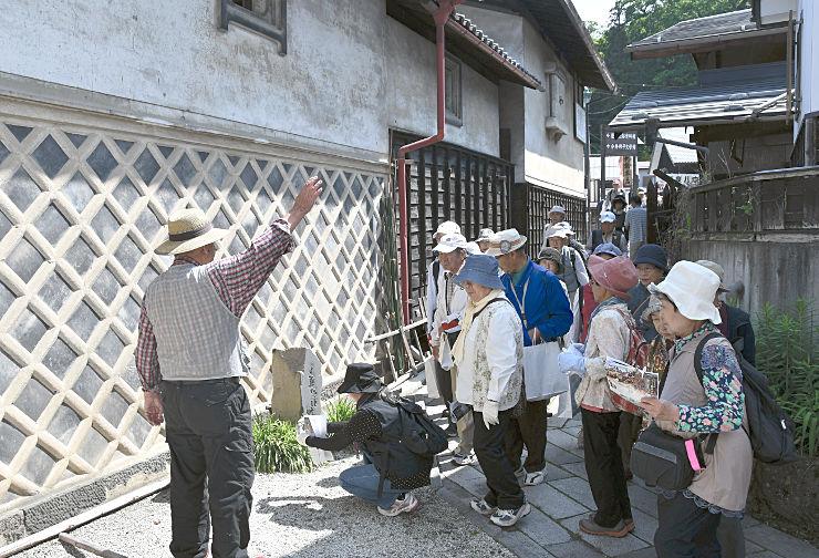 「くら道」と呼ばれる路地で故小沢昭一さんの句碑を見学するツアー参加者=2日、下諏訪町