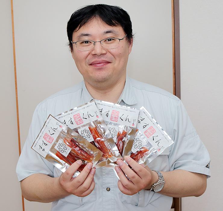 新商品の「ますくん」を手に笑顔を見せる坂井さん