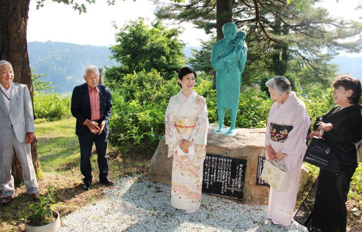 おしん像の前で市民と談笑する俳優の小林綾子さん=3日、十日町市八箇の「あじさい公園」