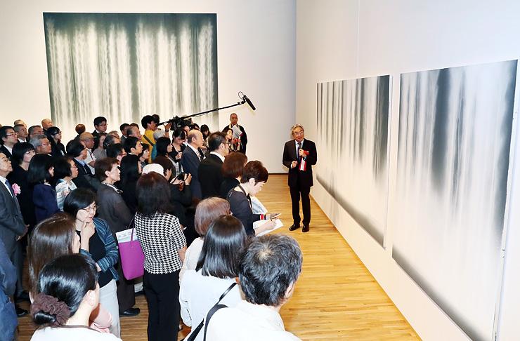千住さん(右)の説明を聞きながら、初公開された襖絵・障壁画「瀧図」に見入る大勢の来場者=富山県美術館