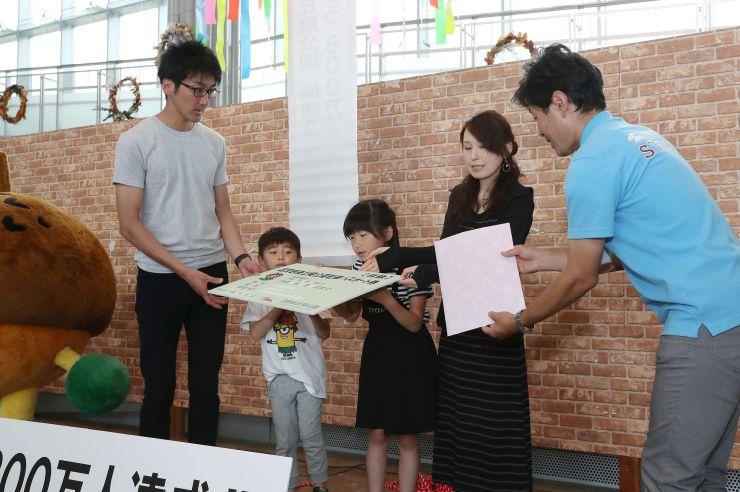 入園者800万人目となり、記念品を受け取る女子児童の一家=10日、長岡市の国営越後丘陵公園