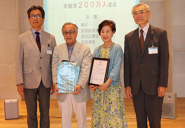 来館200万人目となった荒川さん(左から2人目)と妻の美恵子さん(同3人目)=TOYAMAキラリ