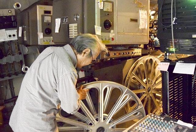 35ミリフィルム映写機で松本零士さん原作の映画を上映する。リールにフィルムを巻き付けセットする=福井県福井市のメトロ劇場映写室