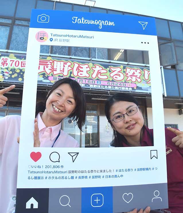 JR辰野駅前でフレームを紹介する町地域おこし協力隊の(左から)柴さん、苫米地さん
