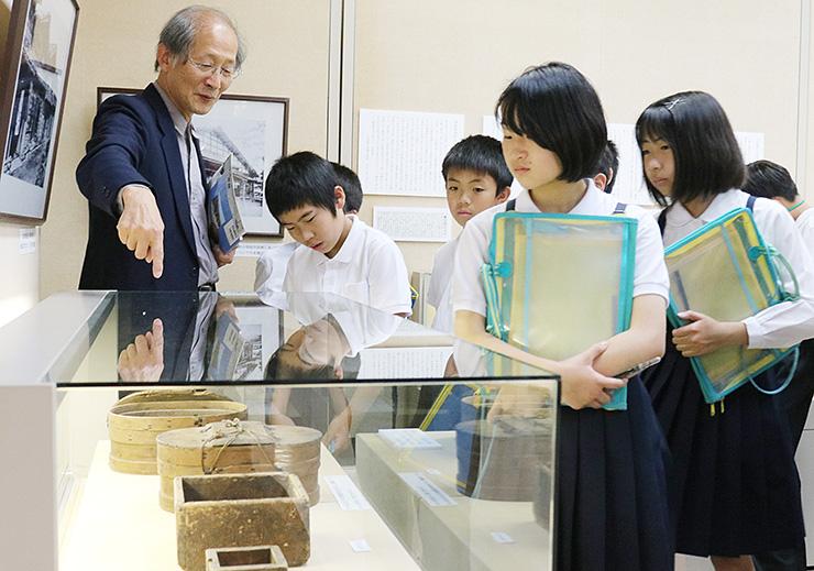 古い写真や道具を通して米騒動の時代背景を語る麻柄館長(左)