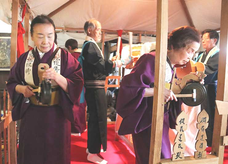 「跡部の踊り念仏」で太鼓の音に合わせてかねを打ち鳴らしながら踊る保存会会員ら=4月1日、佐久市