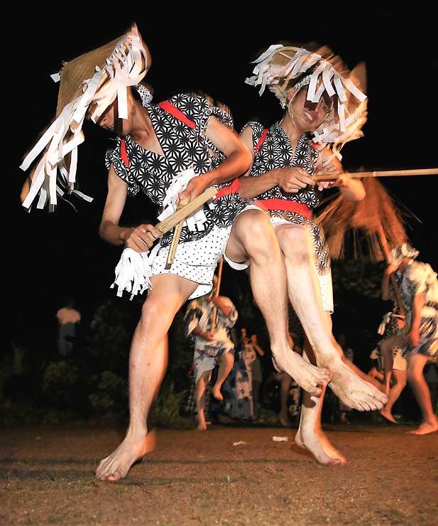 竹で作ったささらと棒を手に、激しく体をぶつけ合ったり、跳ねたりして踊る「和合の念仏踊り」=2017年8月13日、阿南町