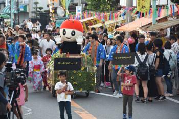 子どもたちの先導でJR辰野駅前商店街をパレードするぴっかりちゃん=16日
