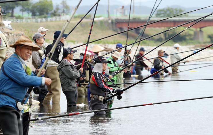 アユ釣りが解禁され、さおを連ねる釣り人たち=高岡市戸出石代の庄川左岸