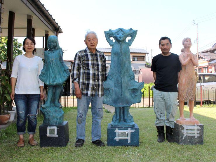 十日町市住吉町の住宅街に飾る彫刻の制作者。左から丸山恵美さん、藤巻秀正さん、角谷豊明さん=同市住吉町