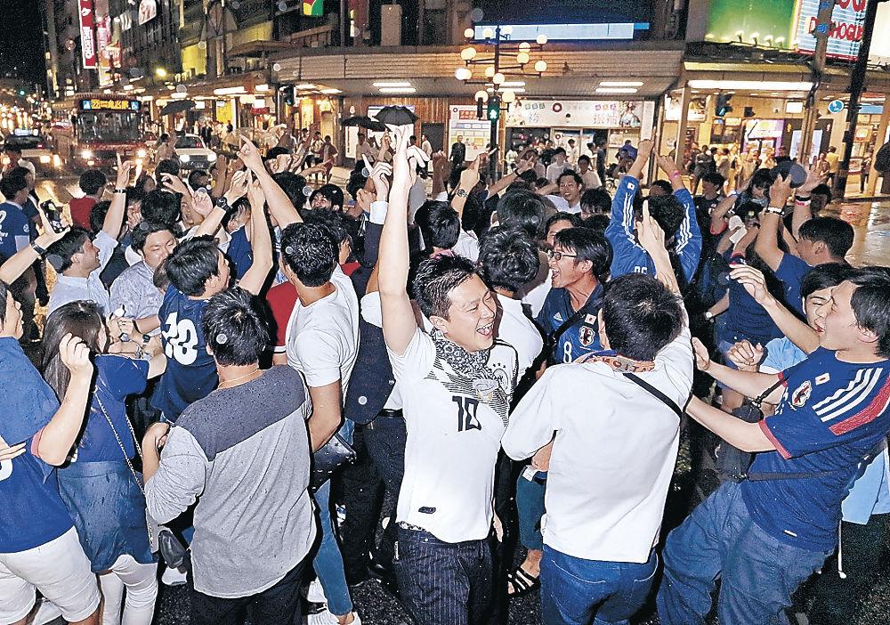 繁華街に続々と集まり、日本の勝利を喜び合う市民=19日午後11時13分、金沢市の片町スクランブル交差点