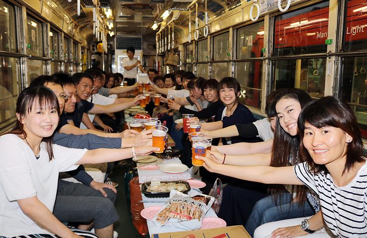出発する万葉線の車内でビールを手に乾杯する乗客=高岡駅