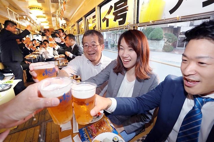 市内電車の中で乾杯する人たち=富山市内