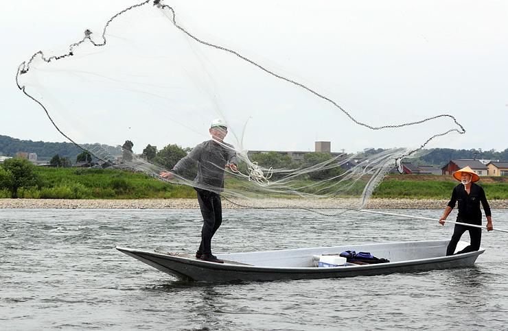 アユの網漁が解禁され、勢い良く投網を放つ愛好者=富山市の神通川有沢橋下流