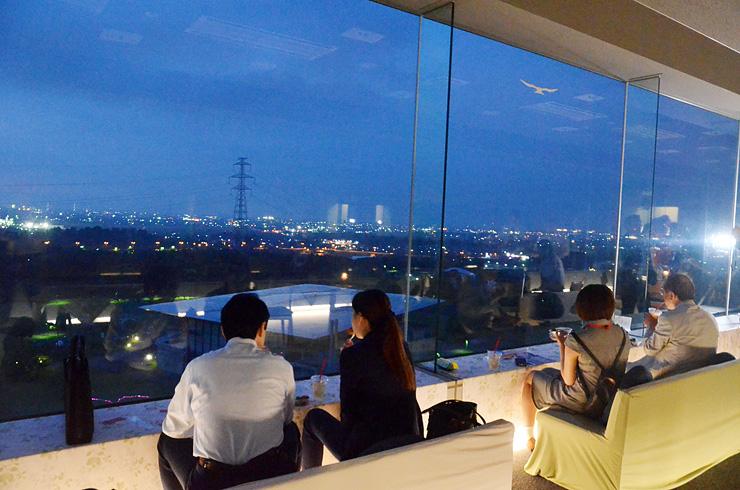 天空カフェの内覧会で夜景を楽しむ参加者たち