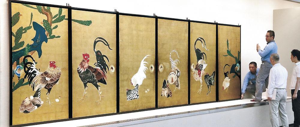 慎重に取り付けられる「仙人掌群鶏図襖」=金沢市の県立美術館