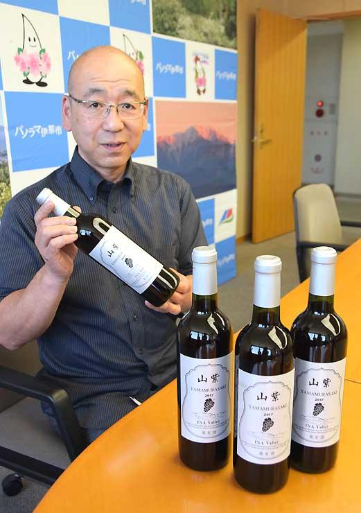 昨年収穫したヤマブドウで造った赤ワイン「山紫」を手にする村田さん