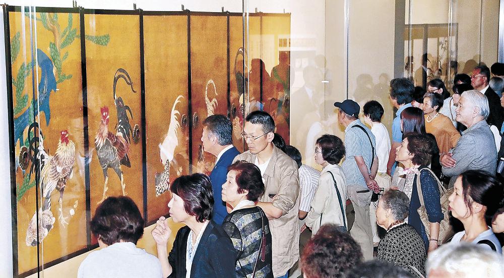 黄金に輝く「仙人掌群鶏図襖」に目を凝らす来場者=金沢市の石川県立美術館