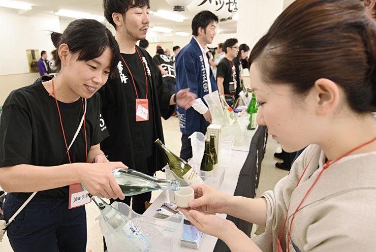 昭和59年生まれの後継ぎがいる酒蔵の日本酒を飲み比べた来場者(右)ら