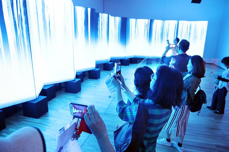 滝をモチーフにした「龍神」をスマートフォンで撮影する来場者=富山県美術館
