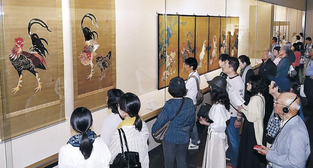 若冲の「仙人掌群鶏図襖」(奥)と光瑤が模写した鶏図(手前)を見比べる来場者=金沢市の県立美術館