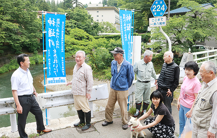 山田川沿いにのぼり旗を立てる住民