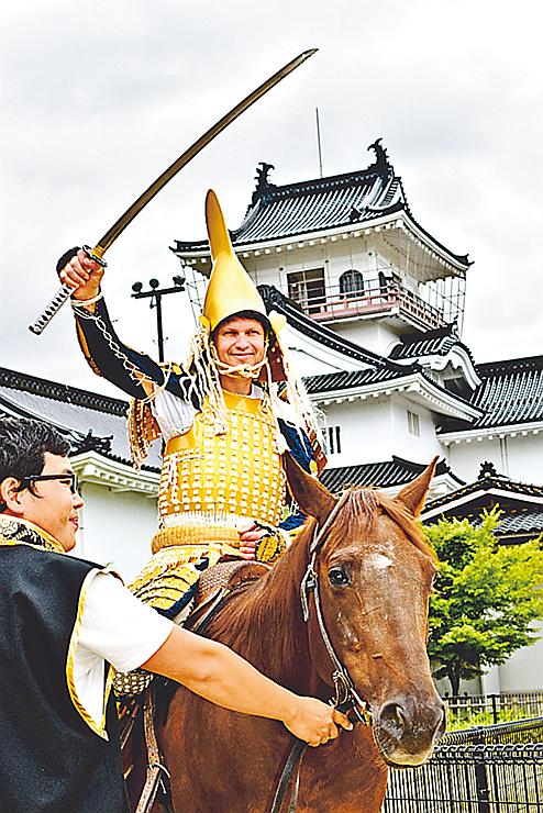 甲冑姿で馬に乗りポーズを決める外国人観光客
