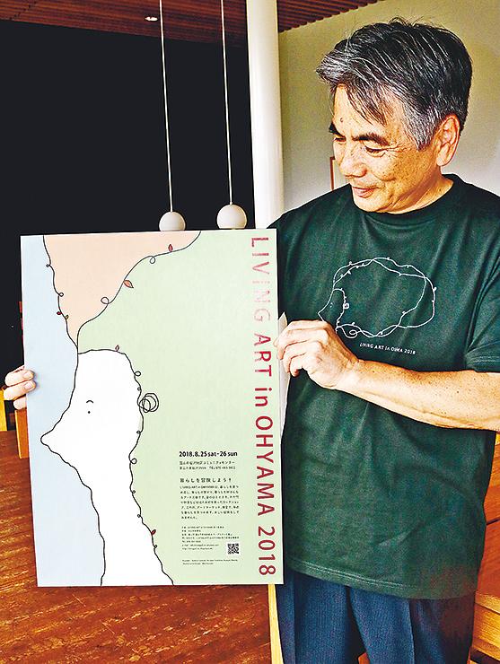 完成したTシャツを着て、ポスターを手にする北村実行委員