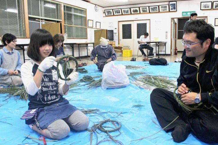30日の茅の輪まつりに向けて、「ミニ茅の輪」作りに励む住民=佐渡市小木町