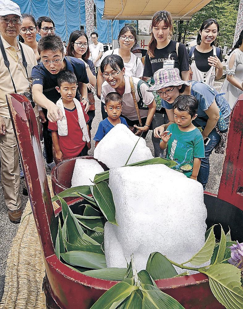 氷室小屋から切り出された雪氷に歓声を上げる来場者=金沢市の湯涌温泉