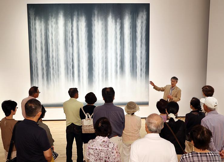 杉野副館長(右奥)の説明を聴きながら、高さが4メートル近い「瀧図」を鑑賞する来場者=富山県美術館