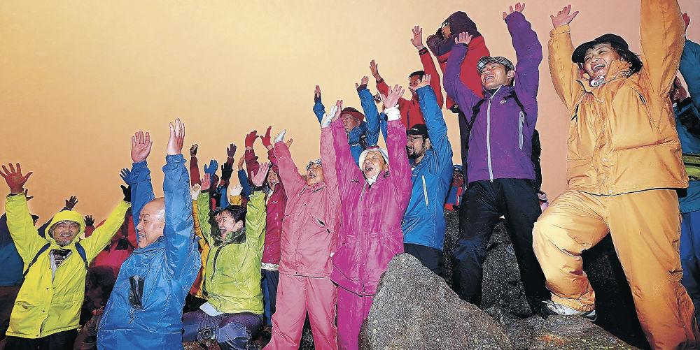 山頂で万歳三唱する登山者=1日午前4時42分、白山・御前峰