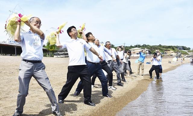 シーズン中の安全と盛況を願いスイカや花束を投げ入れる関係者=7月1日、福井県坂井市の浜地海水浴場