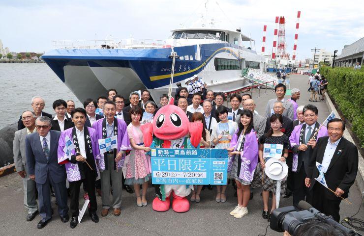 粟島-新潟航路の就航を祝う関係者ら=29日、新潟市中央区の朱鷺メッセ前