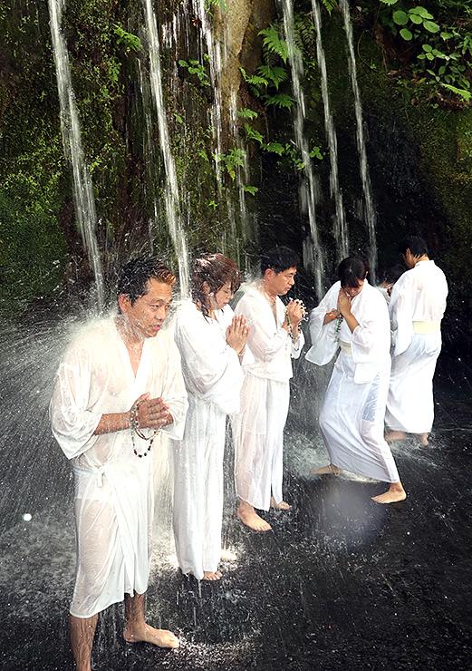 手を合わせ、無心で滝に打たれる参加者=大岩山日石寺