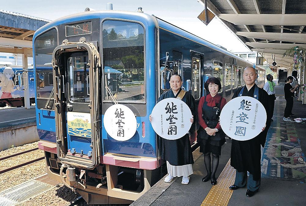 「能登國」のヘッドマークを付けた観光列車と、運行に立ち会った山川執事長(左)、髙島知客(右)=のと鉄道穴水駅