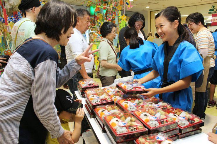 地元の名物などが詰まったうみがたり弁当を販売する子どもたち=上越市