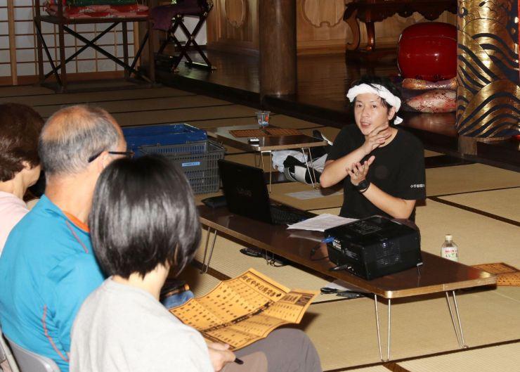 牛の角突き観戦前に、歴史やルールを説明した木島良さん=1日、小千谷市小栗山の福生寺