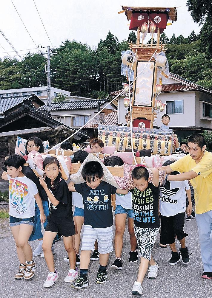 子どもキリコを担いで町内を巡行する小中学生=能登町宇出津