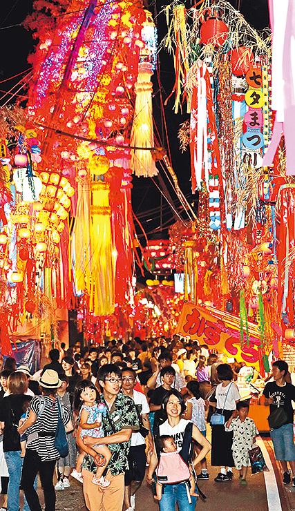 通りを彩る七夕飾りの下を歩く大勢の見物客=高岡市戸出町