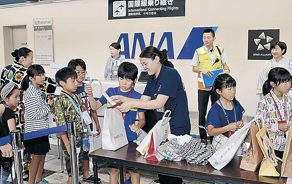 預かり荷物のタグ付けを体験する児童=能登空港