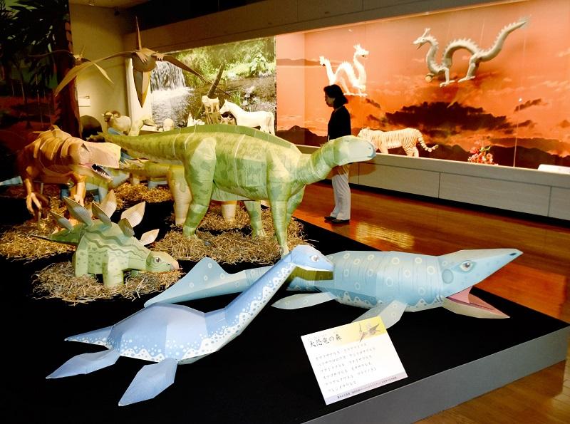 ペーパークラフトの恐竜などが並ぶ作品展=7月7日、福井県越前市武生公会堂記念館