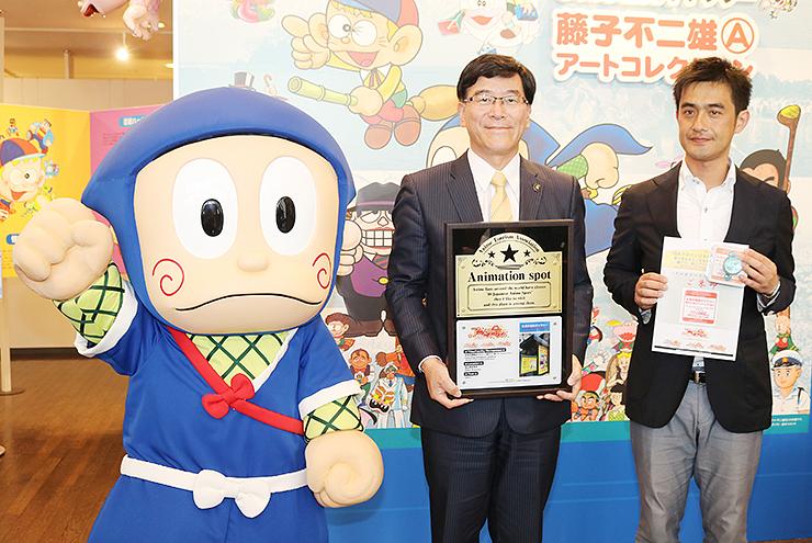 アニメ聖地88の認定プレートを手にする林市長(中央)と、アニメツーリズム協会の寺谷理事=氷見市潮風ギャラリー