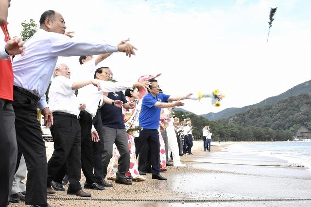 関係者が海に花を投げ入れてシーズン中の無事故とにぎわいを祈願した海開き式=7月8日、福井県敦賀市の気比の松原海水浴場