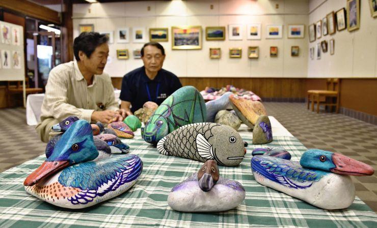 松井武さんが手掛けた石を使った作品や、絵画が並ぶ回顧展=長岡市島崎