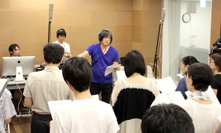 「大地の芸術祭」の開幕を飾るコンサートに向け、地元のコーラス隊を指導する音楽家、小林武史さん(中央)=十日町市の越後妻有文化ホール「段十ろう」