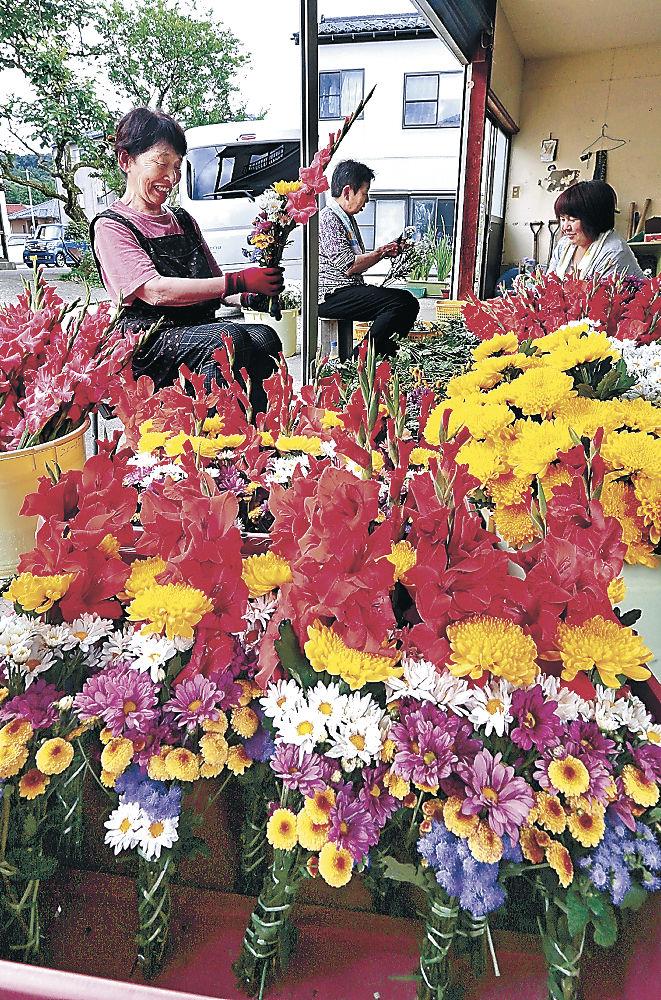 新盆を前に盛んに進められている墓参用の花束作り=金沢市野田町