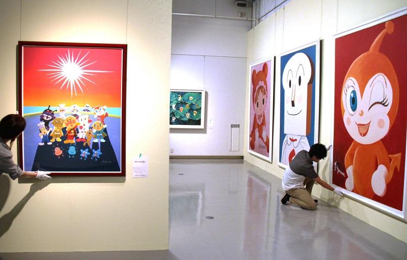 アンパンマンを描いたアクリル画など、多彩な作品の展示作業が進む会場=7月12日、福井県あわら市の金津創作の森