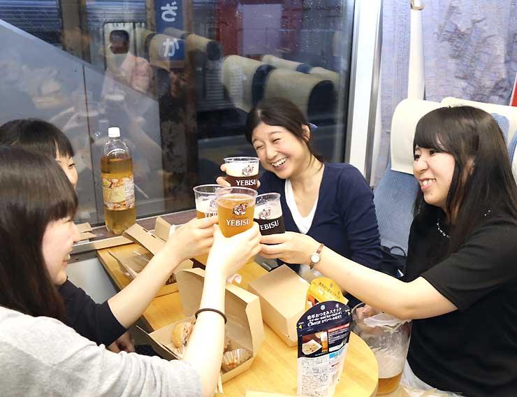 ビアトレインに乗り、ビールで乾杯する乗客ら